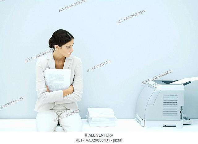 Young woman in suit sitting next to printer