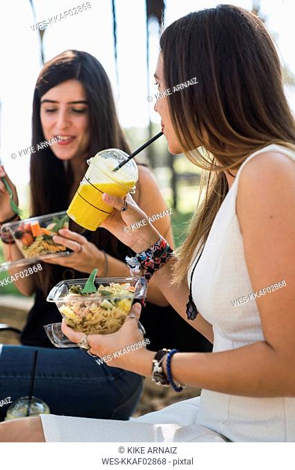 Girl friends sitting in a park, eating salad,, drinking juice