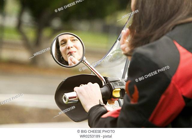Woman applying lipstick in motorcycle mirror