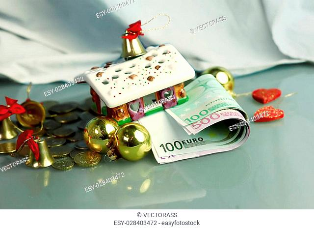 Christmas House with euro banknotes and coins around, concept of holidays expenses and gifts