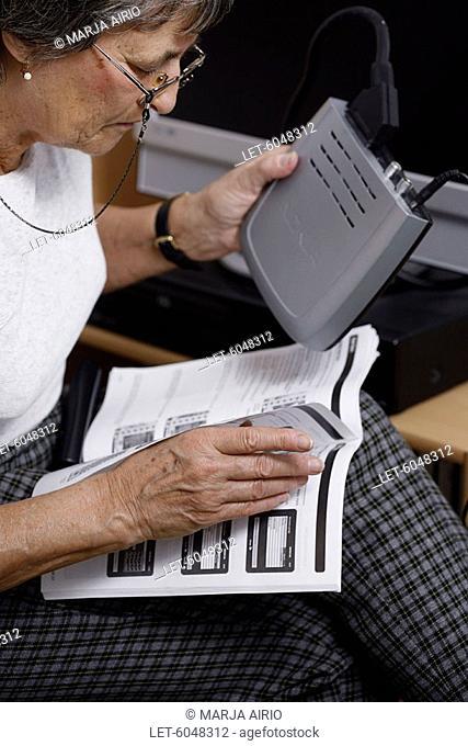 Digital television  Elderly woman studying DVB receiver instruction book