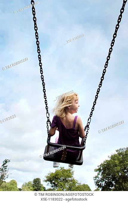 Rearview 7 year girl riding high on swing in childrens playground