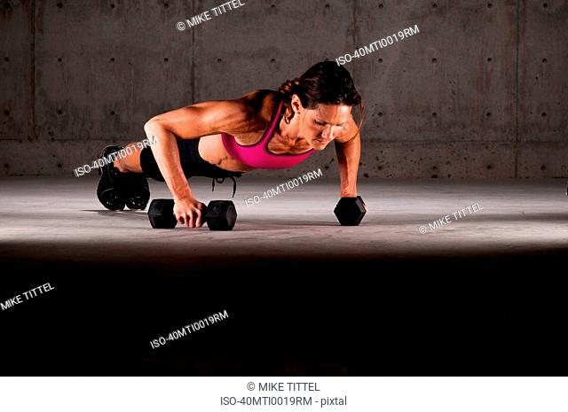 Woman doing push ups on weights