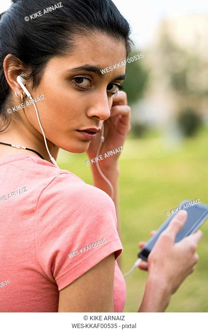 Portrait of female athlete with earphones and cell phone