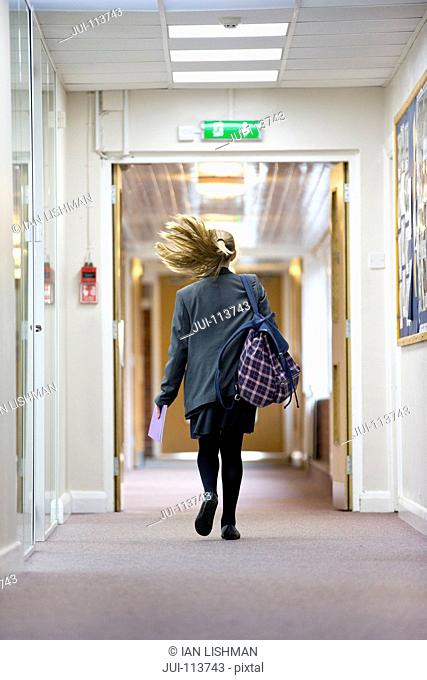 Middle school student running in school corridor