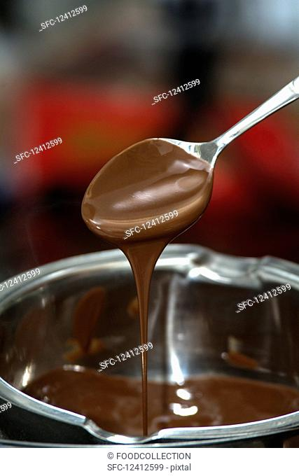 Melted chocolate dripping from a spoon into a bowl