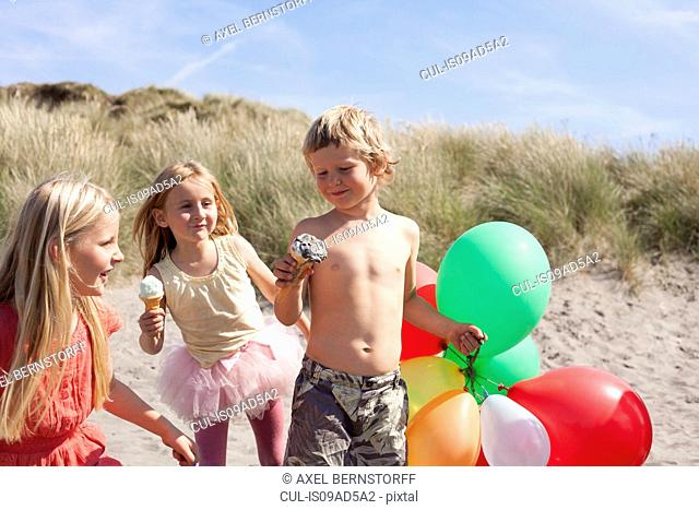 Three children eating ice creams on beach with balloons, Wales, UK