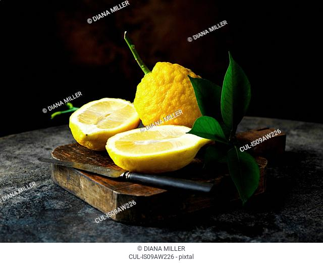 Textured lemon whole and halved with leaves on wooden chopping board with vintage knife