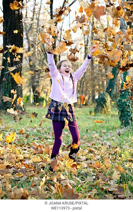 girl is playing in the woods with autumn foliage