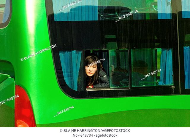 Woman looking out of a bus window, Shanghai, China