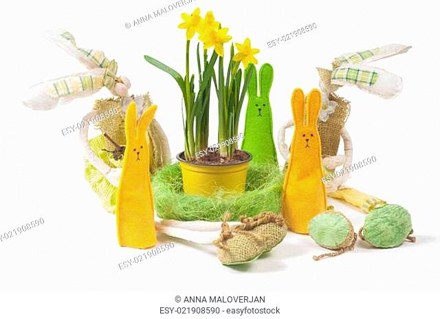 Yellow narcissus in the pot and five bunnies