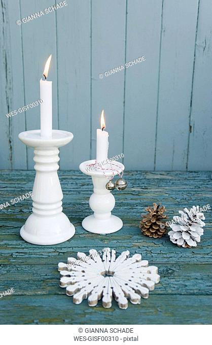 White table mat, made of clothespins, white candles, bells and fir cones