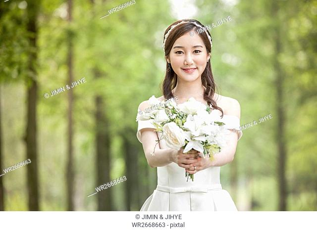 Young smiling bride holding flowers outdoors