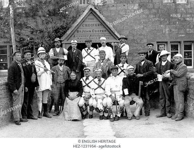 The Headington Quarry Morris Dancers posing with locals outside the public house entrance to the Chequers, Oxford, Oxfordshire, c1860-c1922