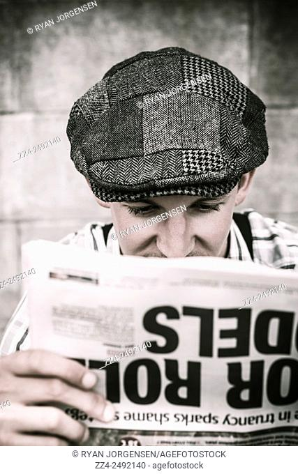 Old style image on the face of a man reading broadsheet newspaper in back alley location. Back when news was true