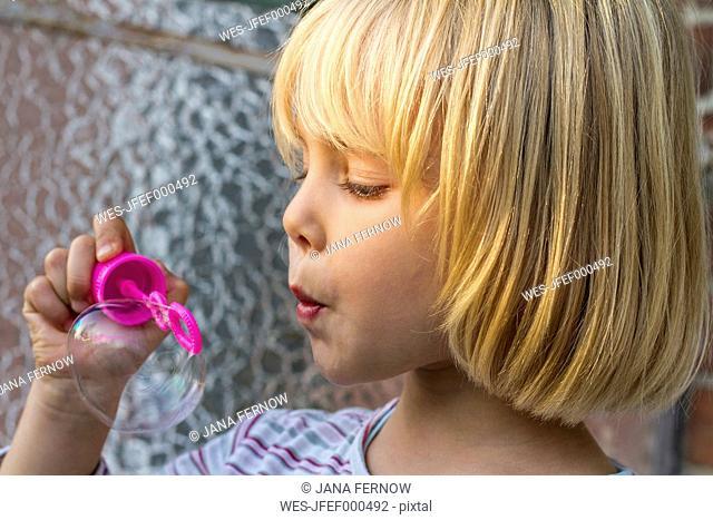 Portrait of little girl making soap bubbles