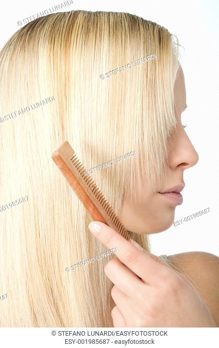 Beautiful blonde woman brushing her hair