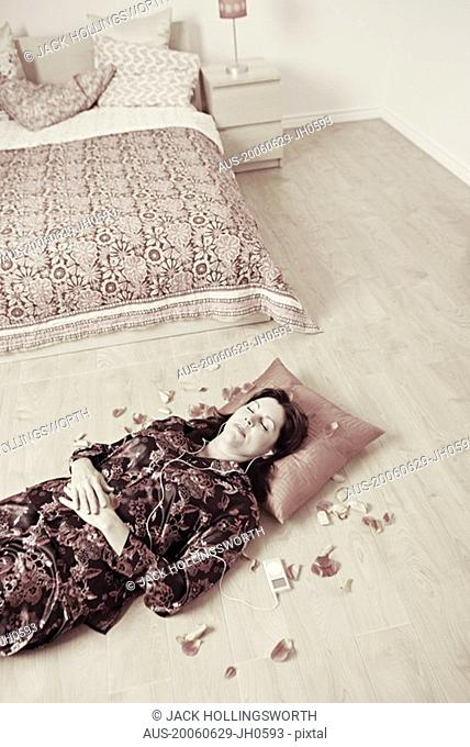 High angle view of a mature woman lying on a wooden floor and listening to an MP3 player