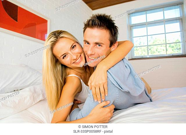 Smiling couple hugging in bed