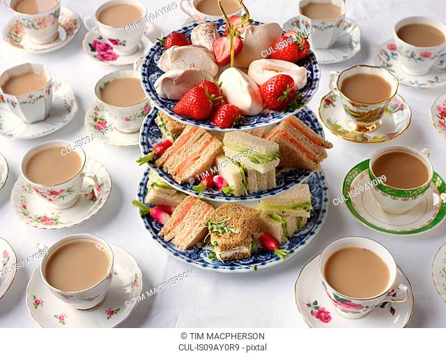 Vintage tea cups and sandwiches on cakestand prepared for afternoon tea