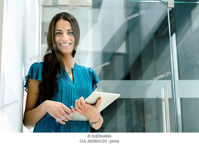 Window view portrait of young businesswoman with digital tablet at office entrance