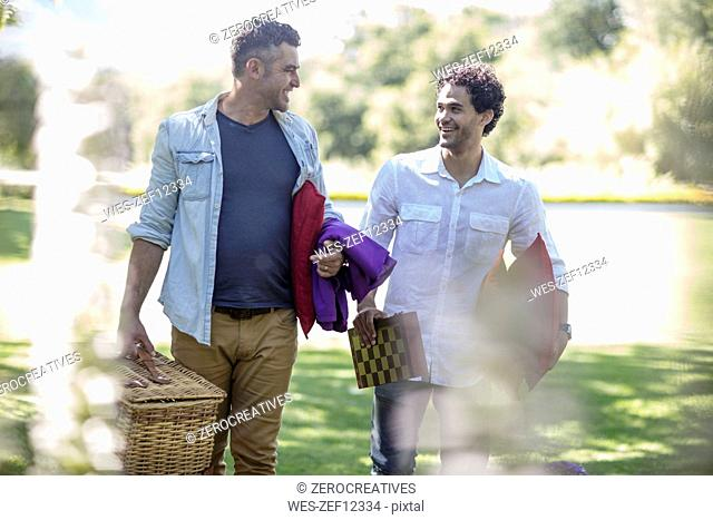 Two friends walking in park with picnic basket and chessboard
