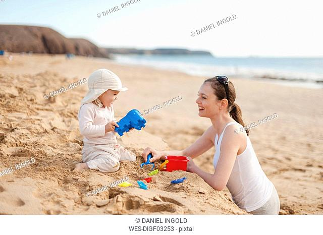 Mother playing with little daughter on the beach