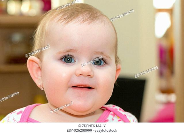 Happy cute little one year old girl indoor in white pink dress