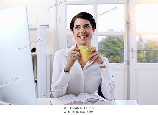 Smiling woman holding cup of coffee at desk in office