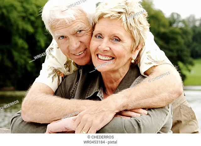 Portrait of a senior man embracing a senior woman from behind