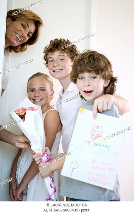 Children giving mother flowers and hand-made greeting card