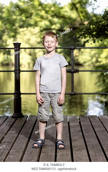 Portrait of little boy standing on footbridge in a park