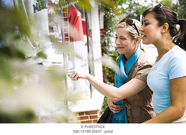 Two women looking at the window display of store