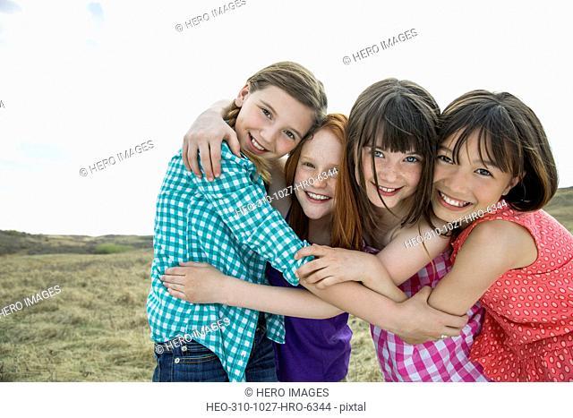 Portrait of playful schoolgirls embracing during field trip