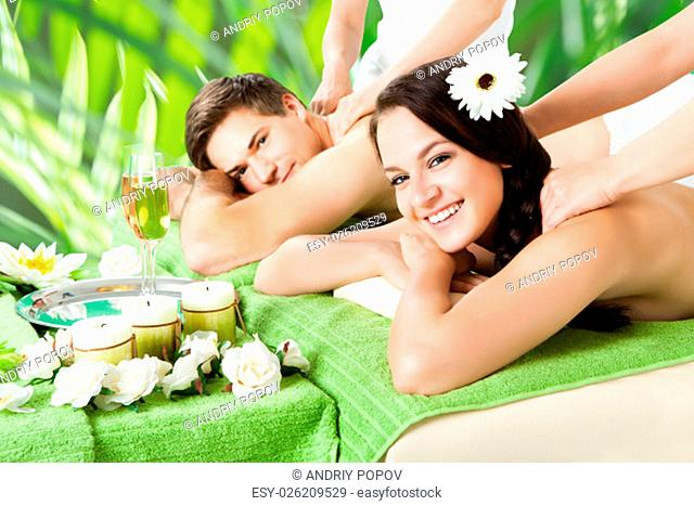 Portrait of smiling young couple receiving shoulder massage at beauty spa