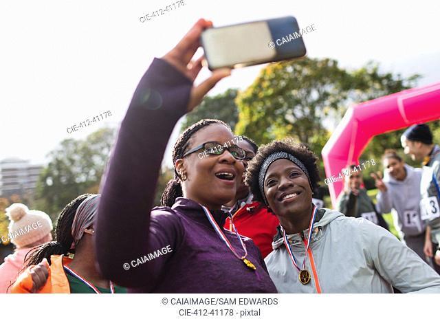 Female runner friends taking selfie at charity run in park