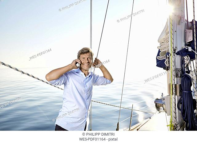 Portrait of smiling mature man lon the phone on his sailing boat