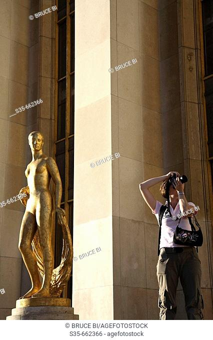 A visitor taking photo beisde a gilded bronze statue in the central square of the Palais de Chaillot. Paris. France