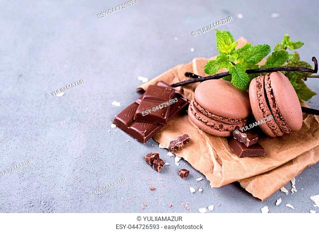 Chocolate macaroons with pieces of black chocolate, vanilla stick and mint on a stone background