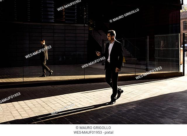 Businessman walking in the city checking cell phone