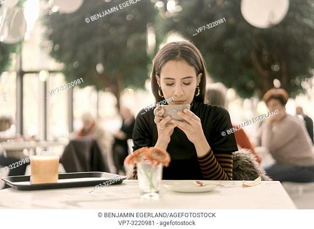 woman drinking coffee while sitting at table in coffee house, in Munich, Germany