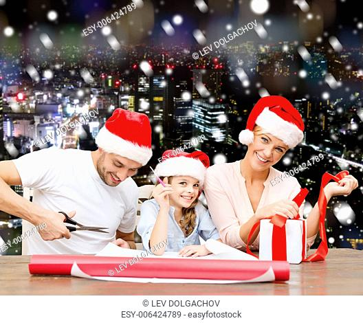 christmas, holidays, family and people concept - happy mother, father and little girl in santa helper hats with gift box and scissors over snowy night city...