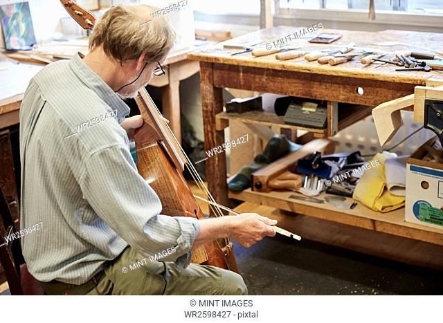 A violin maker in his workshop playing an instrument with a bow, tuning and finishing