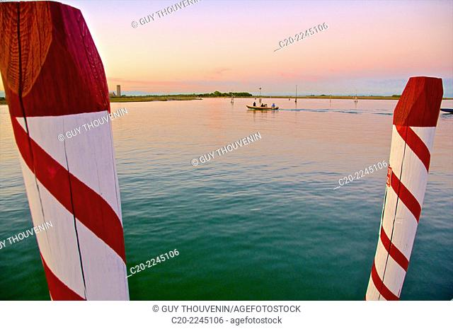 Laguna at sunset with red and white Paline, mooring posts, Venice, Italy