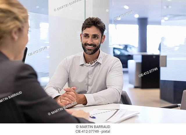 Smiling male customer listening to car saleswoman in car dealership office
