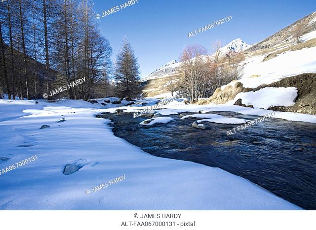 Snow-covered rocks in river in snowy landscape