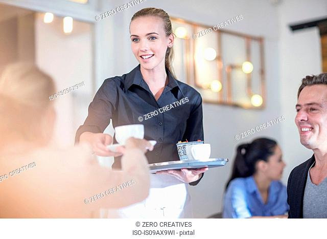 Waitress serving coffee to customers in restaurant