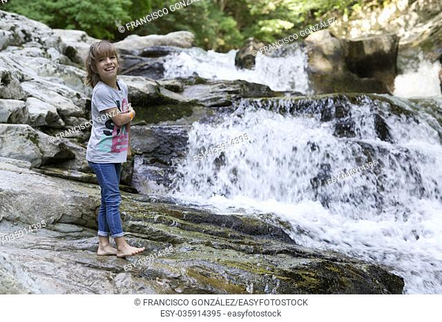 Girl next to the Waterfall of the bucket in the Selva de Irati in Navarra, Spain