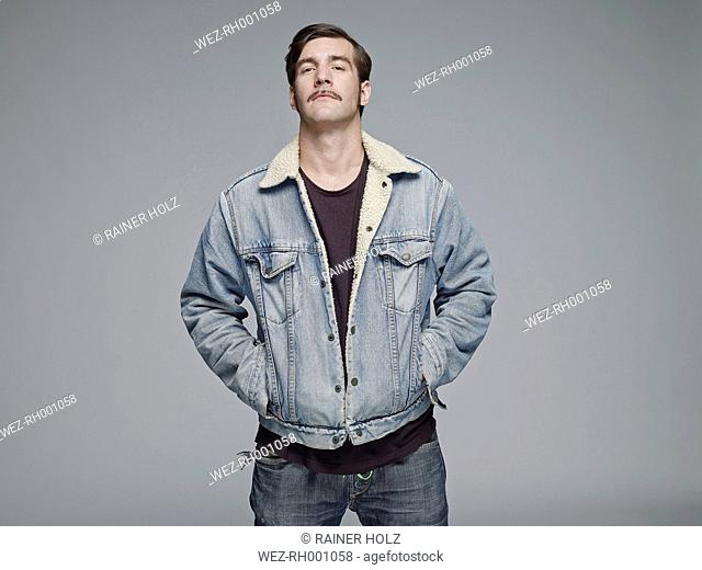 Portrait of man wearing jeans jacket in front of grey background