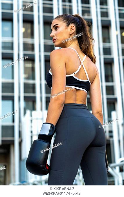 Sportive young woman with boxing gloves in the city in front of a high-rise building